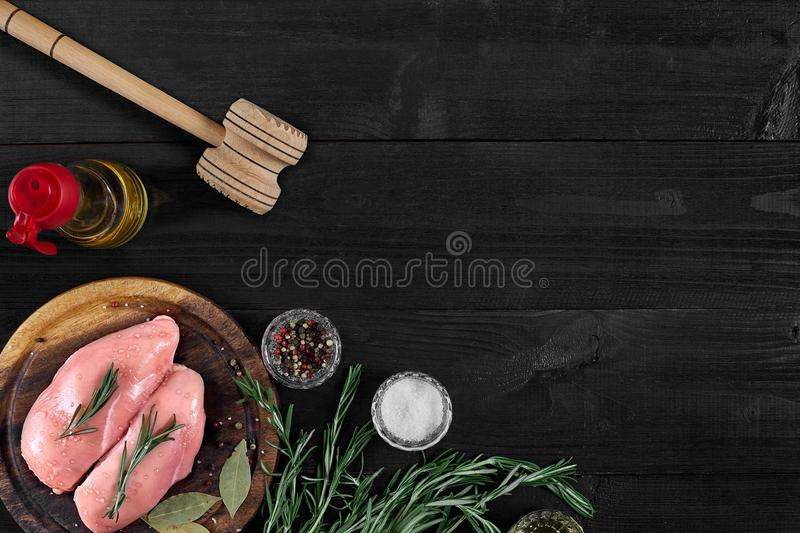 Raw chicken breast fillets on wooden cutting board with herbs and spices. Top view with copy space stock photos