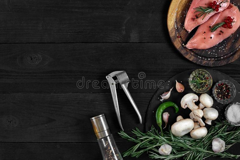 Raw chicken breast fillets on wooden cutting board with herbs and spices. Top view with copy space royalty free stock image