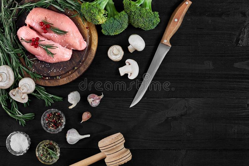 Raw chicken breast fillets on wooden cutting board with herbs, spices and vegetables. Top view with copy space stock image
