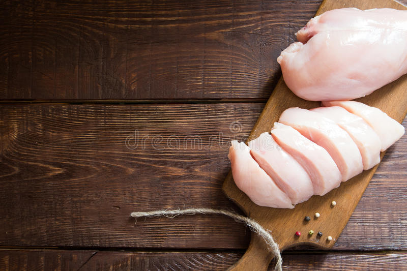 Raw chicken breast fillets on wooden cutting board. royalty free stock photography
