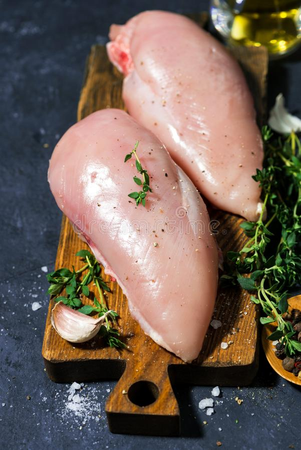 Raw chicken breast and fresh thyme on a cutting board, closeup stock photos