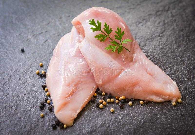 Raw chicken breast with herbs and spices on black plate - Raw uncooked chicken meat marinated with ingredients for cooking royalty free stock images