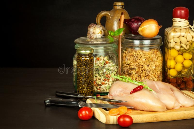 Raw chicken breast on the kitchen board. Diet food. Sale of meat. Spices for preparing meat on grill. royalty free stock photos