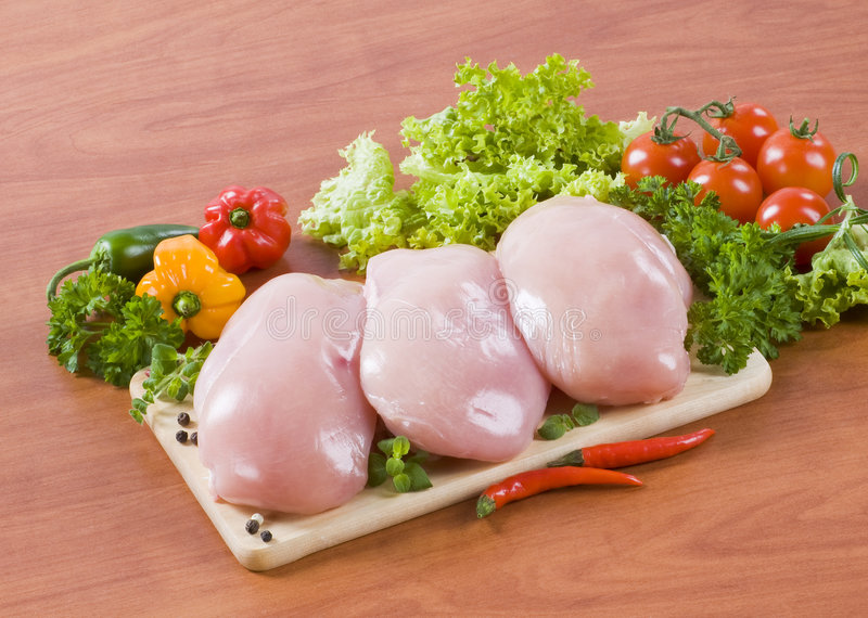Raw chicken breasts. And fresh vegetable stock images