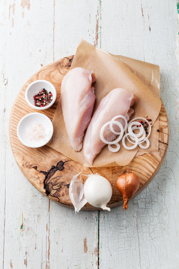 Raw chicken breasts fillets. With onion and pepper on wooden cutting board on blue background stock image