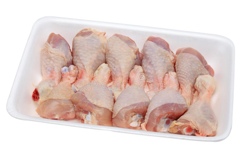 Raw chicken drumsticks. Image of a polystyrene tray with raw chicken drumsticks isolated against a white background.The file include clipping path stock photos