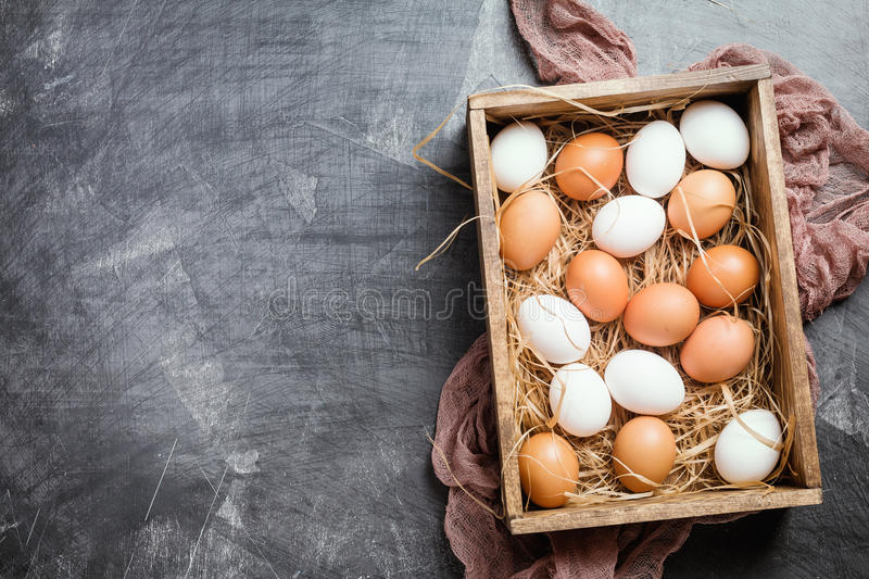 Raw chicken eggs. In a box on black background, top view stock images