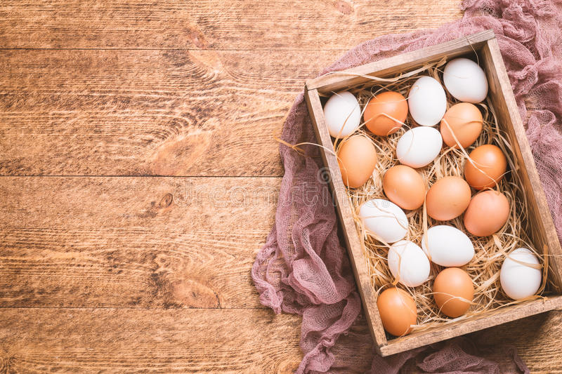 Raw chicken eggs. In a box on rustic wooden background, top view stock photos