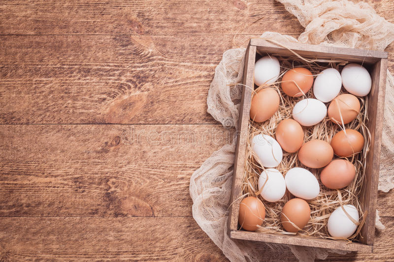 Raw chicken eggs. In a box on rustic wooden background, top view stock image