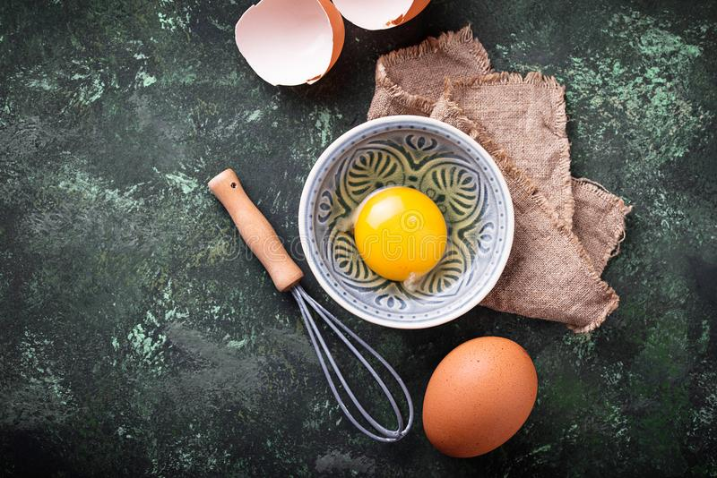 Raw chicken eggs and whisk. Selective focus royalty free stock photo