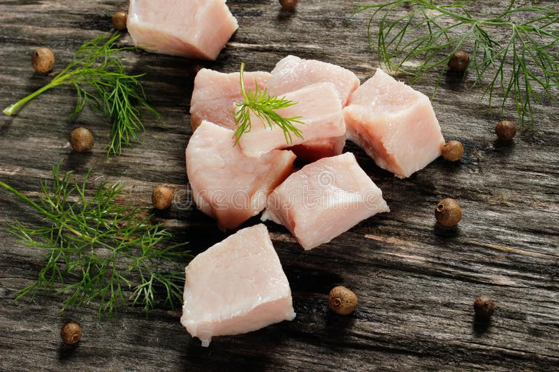 Raw chicken fillet cut into cubes with spices on a wooden surface royalty free stock images