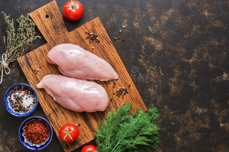 Raw chicken fillet on a cutting board with spices on a dark background. Top view, copy space, flat lay. stock images