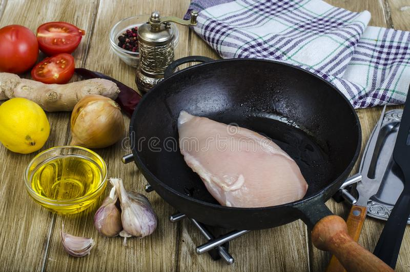 Raw chicken fillet in frying pan, spices stock photo