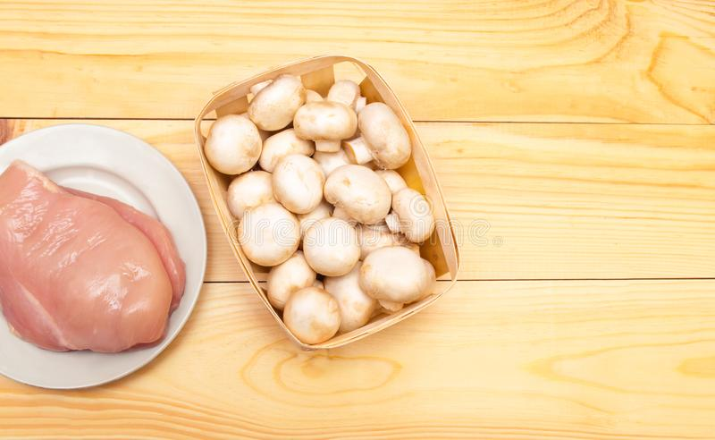 Raw chicken fillet and mushrooms on a wooden background. place f stock photo