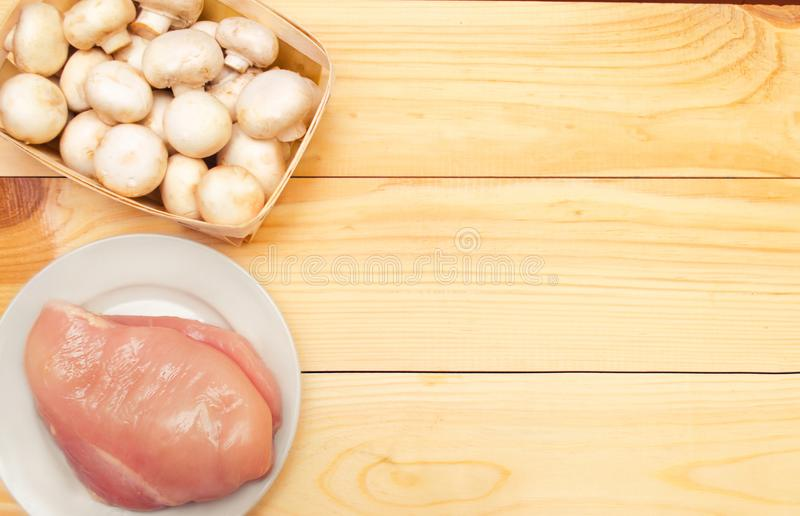 Raw chicken fillet and mushrooms on a wooden background. place f stock photography