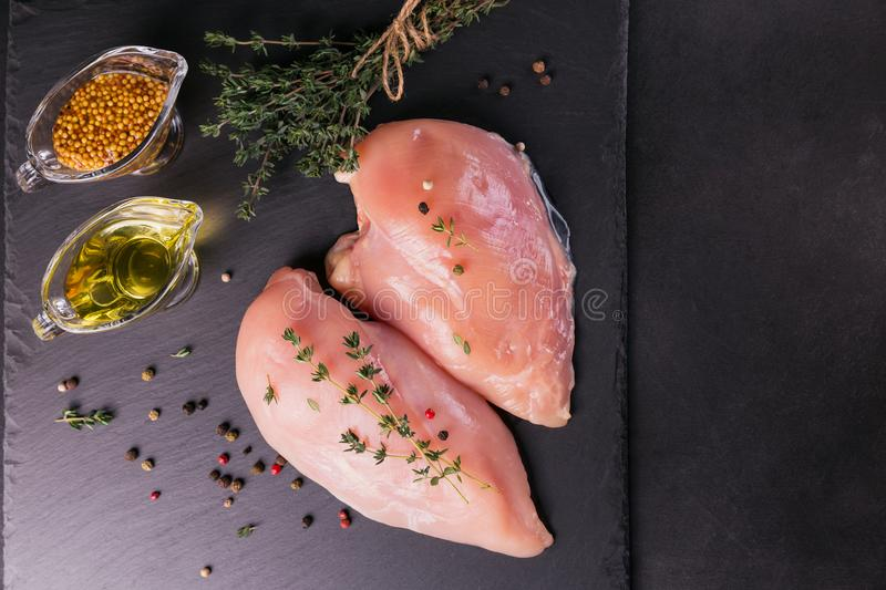 Raw chicken fillets with spices and herbs. stock photo