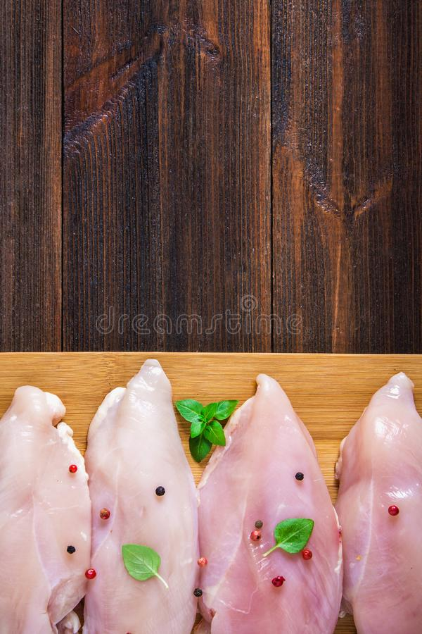 Raw chicken fillets on a cutting board against the background of a wooden table. Meat ingredients for cooking. Empty place for an stock images