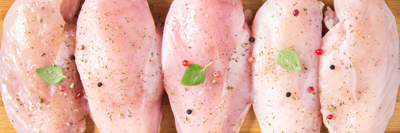 Raw chicken fillets on a cutting board against the background of a wooden table. Meat ingredients for cooking. Flat lei. Top view. stock images