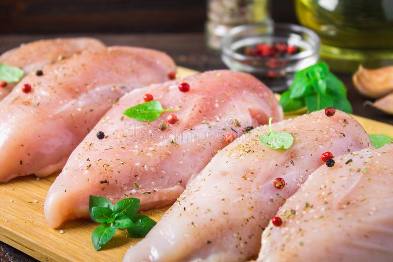Raw chicken fillets on a cutting board against the background of a wooden table. Meat ingredients for cooking. royalty free stock photos