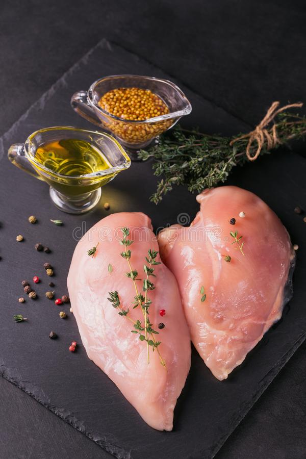 Raw chicken fillets with spices and herbs. royalty free stock photography