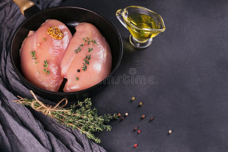 Raw chicken fillets with spices and herbs. stock photography
