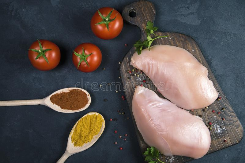 Raw chicken fillets on wooden cutting board with spices in spoons and tomatoes, top view stock photography