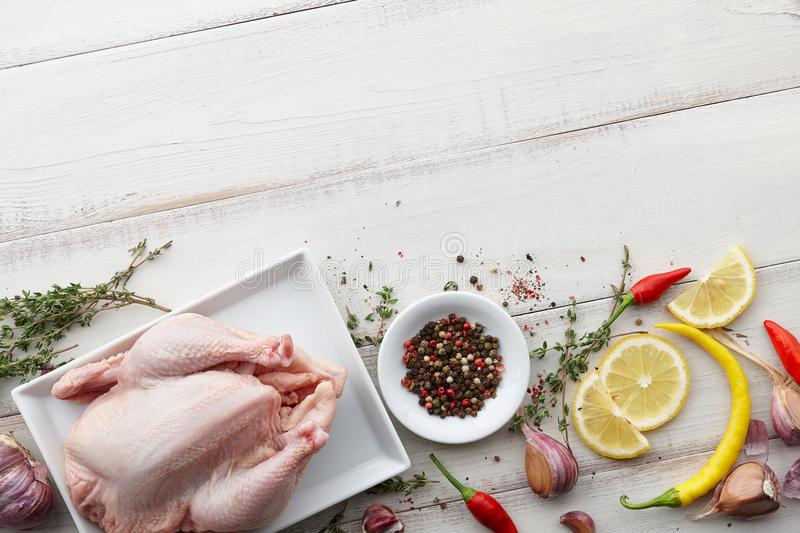 Raw chicken, herbs and spices on white wooden background royalty free stock images