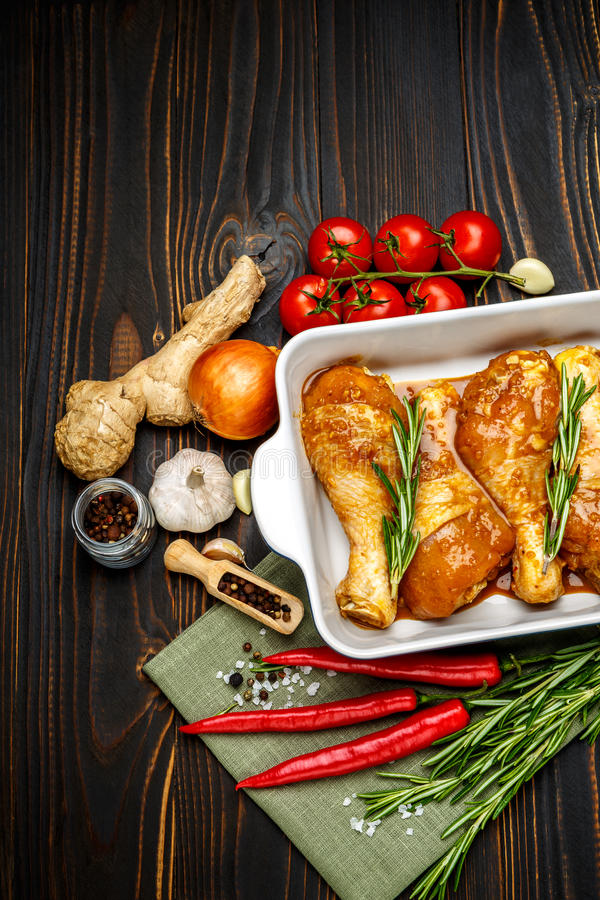 Raw chicken legs in baking dish on a wooden background royalty free stock photos