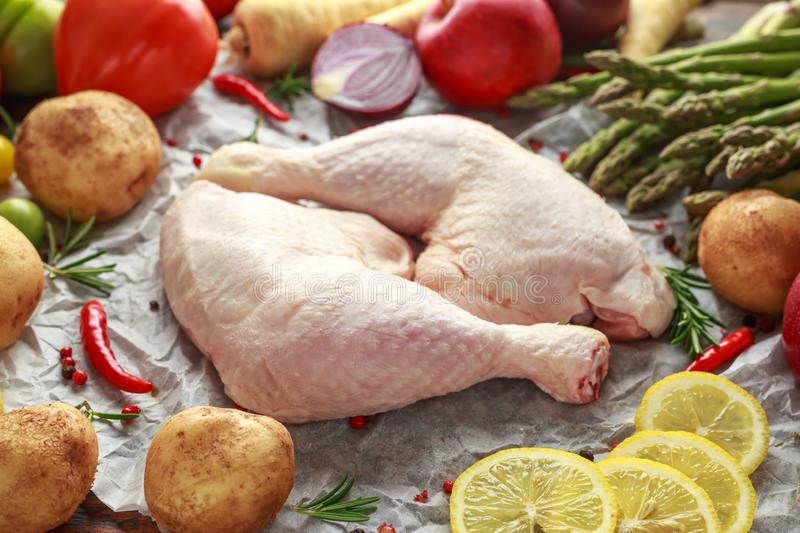 Raw Chicken Legs on baking paper with variety of vegetables stock photography