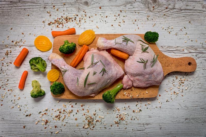 Raw chicken legs from vegetables to a wooden table royalty free stock image