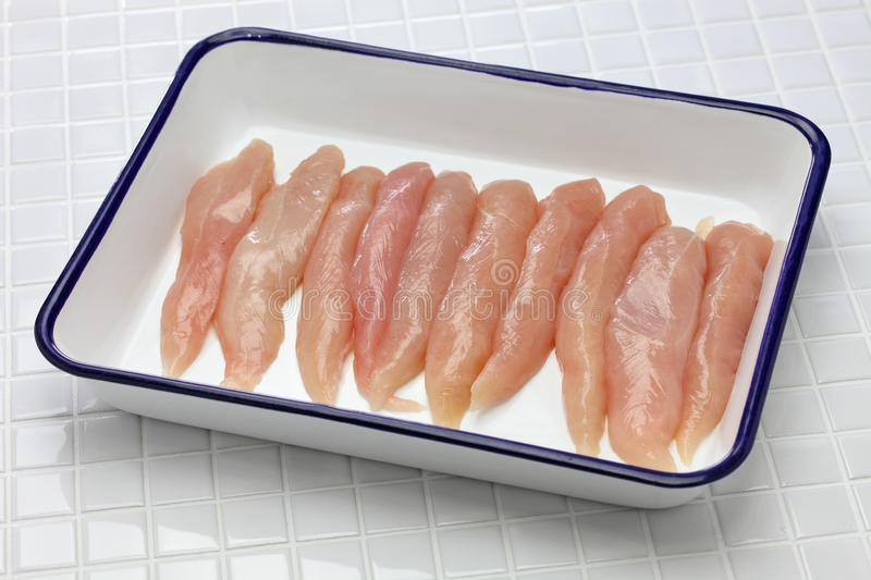 Raw chicken tenders. On butcher tray stock image