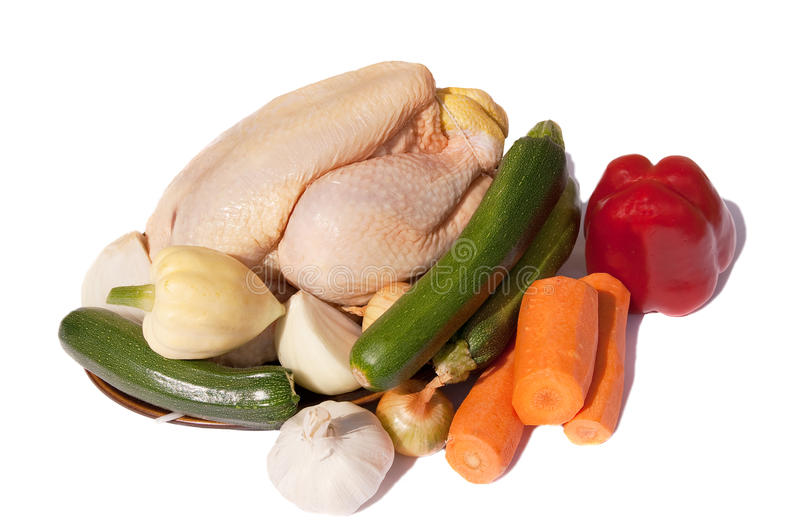 Raw chicken & vegetables for roasting. Raw corn-fed chicken and mixes fresh vegetables for a roast dinner royalty free stock image