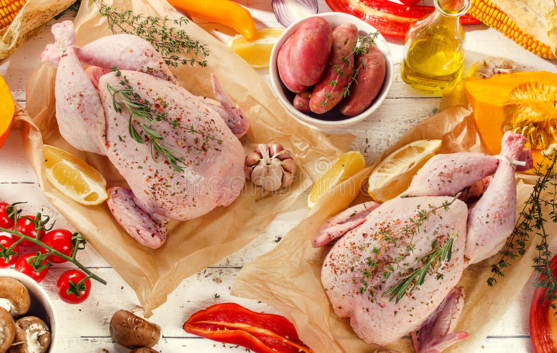 Raw chicken with vegetables. And spices on a white wooden board. Flat lay stock image