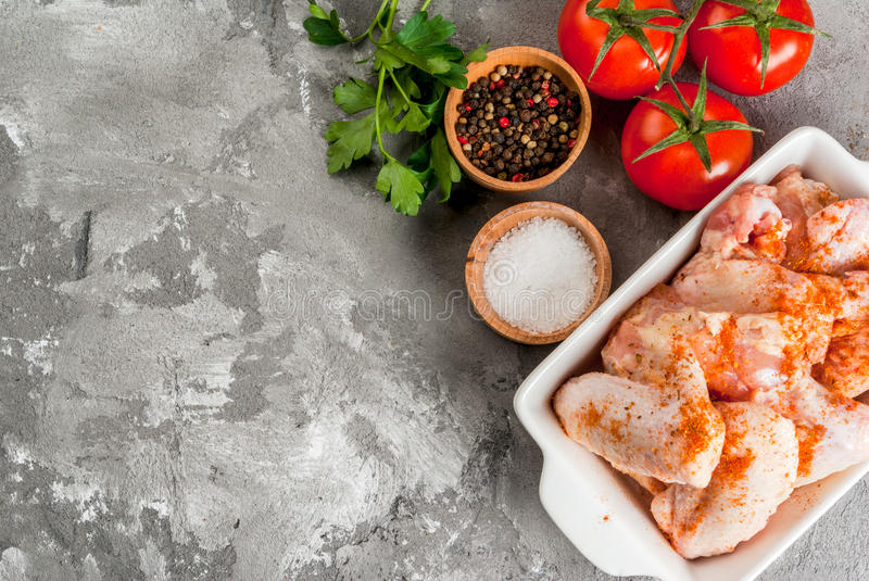 Raw chicken wings in a baking dish. Fresh raw chicken wings in a baking dish, with vegetables for cooking - tomatoes, parsley. top view. On the concrete black royalty free stock images