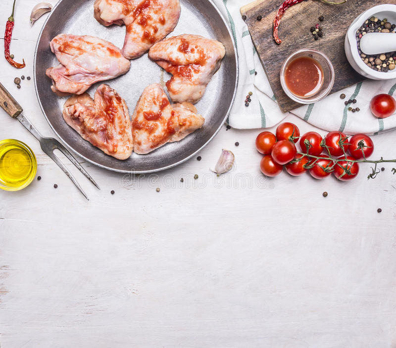 Raw chicken wings in barbecue sauce in the pan, with vegetables and spices wooden rustic background top view close up stock photos
