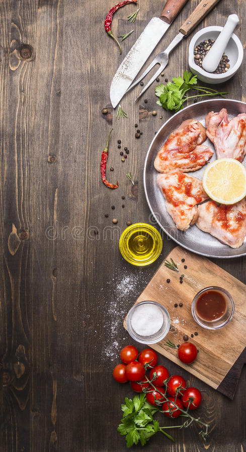 Raw chicken wings in barbecue sauce in a pan with vegetables, spices on wooden rustic background top view close up. Raw chicken wings in barbecue sauce in a pan royalty free stock photos