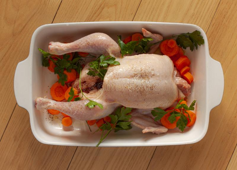 Raw chicken withwith vegetables and olive oil in a baking dish ready to be prepared for cooking. Top view image on wooden backgrou stock photos