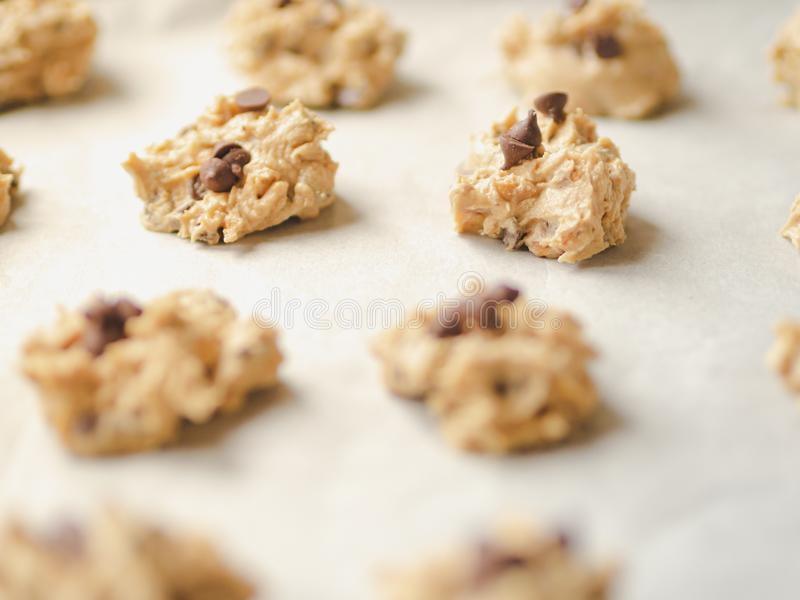 Raw chocolate chips cookie dough on wax paper in a black baking tray. stock photos