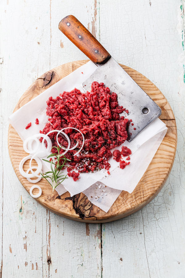 Raw chopped meat and meat cleaver. On wooden cutting board on blue background stock photo