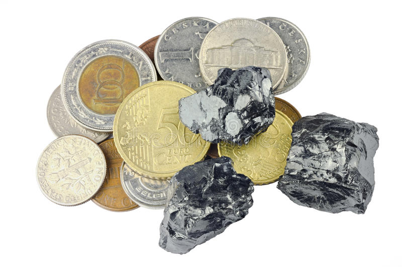 Raw coal nuggets on different coins on top isolated on white background.  stock photography