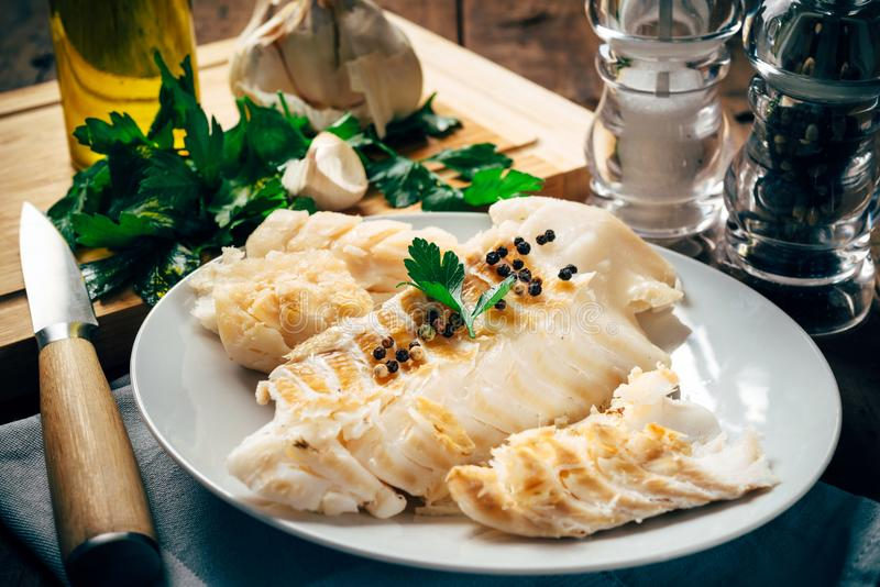 Raw cod fillet on white plate stock photo