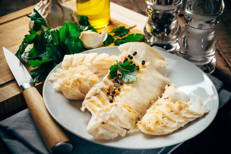 Raw cod fillet on white plate stock image