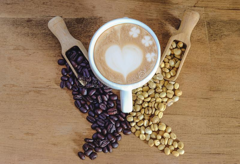 Raw coffee bean and roasters coffee bean in wood spoon and hot late art coffee. On table royalty free stock images