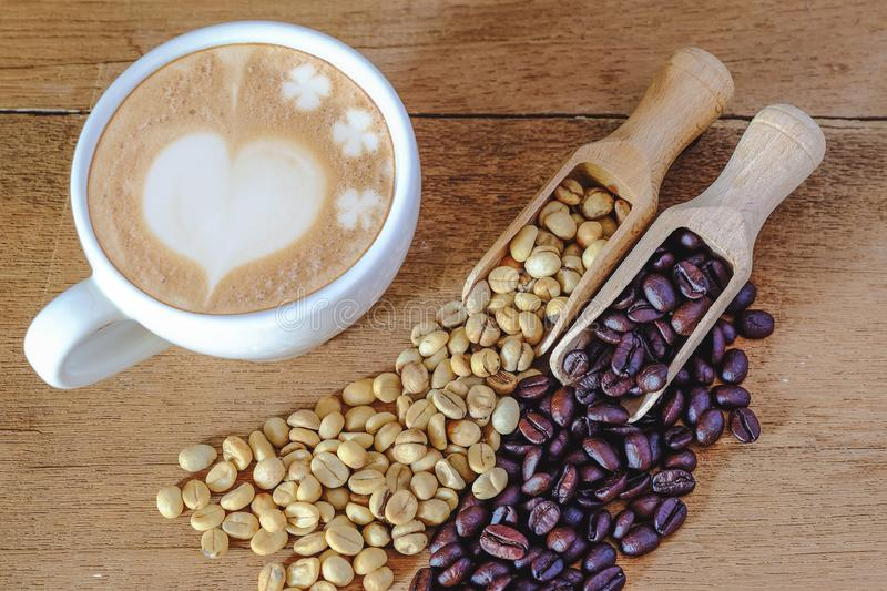 Raw coffee bean and roasters coffee bean in wood spoon and hot late art coffee. On table royalty free stock image