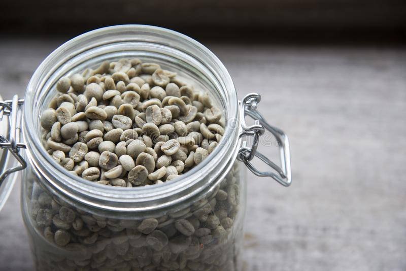 Raw coffee beans,unroasted coffee beans in glass jar on wooden table royalty free stock image