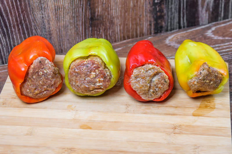 Raw Colored bell peppers stuffed with meat on a cutting Board. Semi-finished products royalty free stock photo