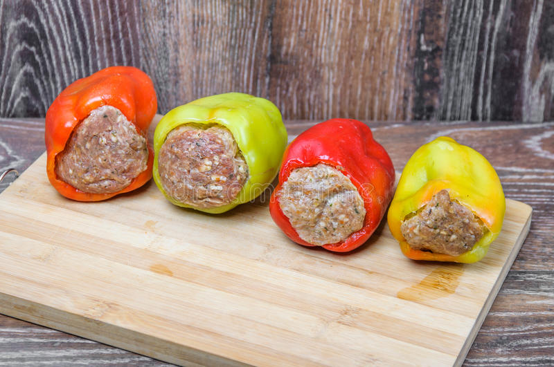 Raw Colored bell peppers stuffed with meat on a cutting Board. Semi-finished products stock images