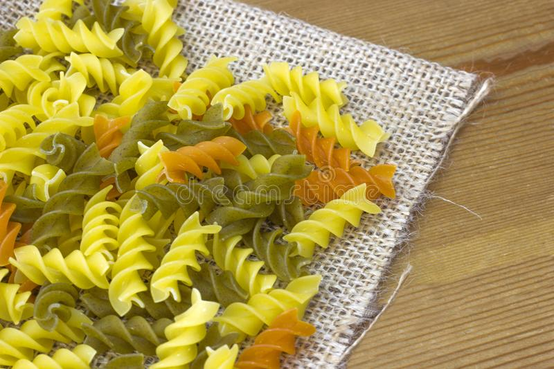 Raw colored fusilli pasta on burlap with close-up stock image