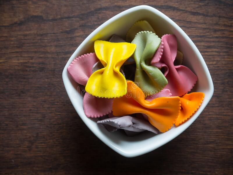 Raw colorful pasta. In a white bowl standing on a wooden table stock images