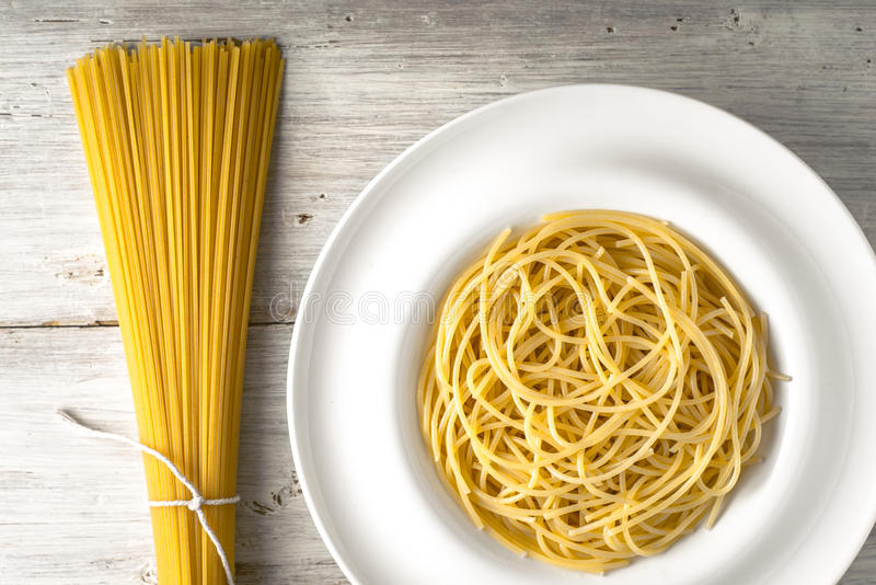 Raw and cooked spaghetti on the white wooden table horizontal. Raw and cooked spaghetti un the white wooden table top view horizontal royalty free stock photos